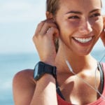 A cheerful young woman putting her earphones in before a running session