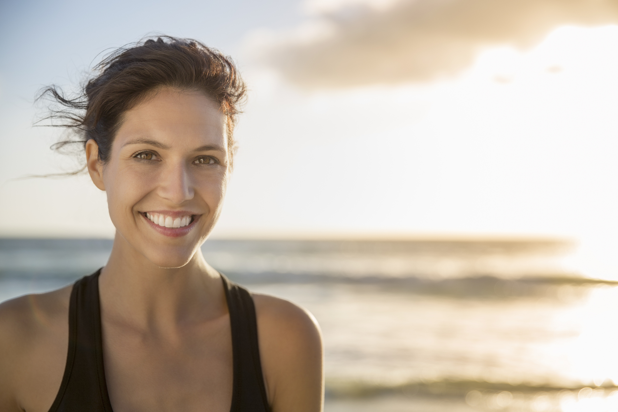 Portrait of happy female athlete at beach. Confident young woman is against sky during sunset. She is sportswear.