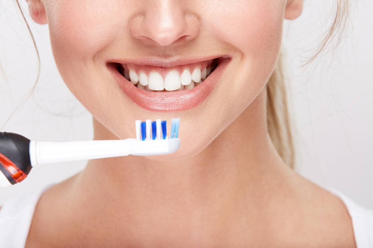 Close up photo of girl with snow white teeth on white studio background, dentistry concept, perfect smile, holding electricity toothbrush.